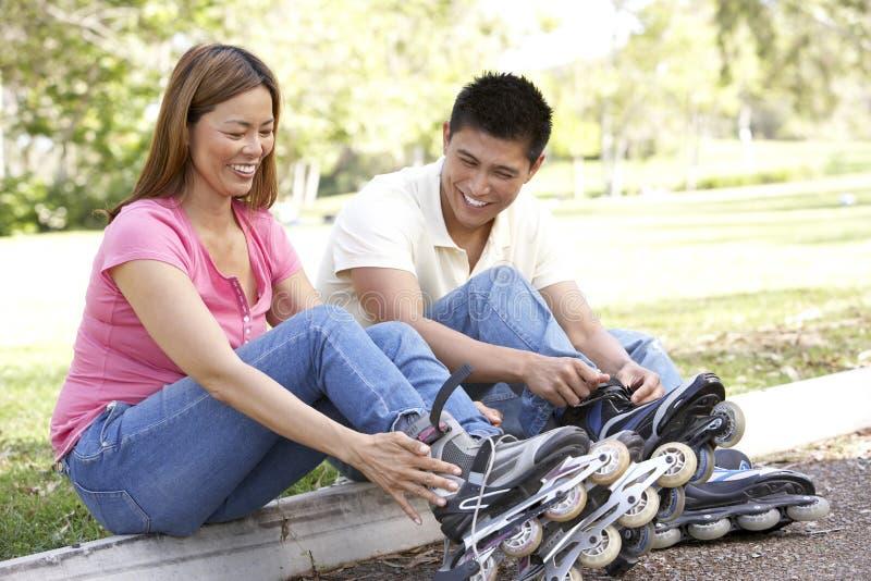 夫妇线路放置冰鞋的公园 免版税库存照片
