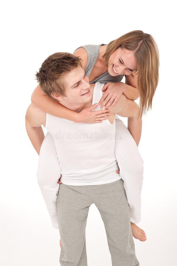 夫妇肩扛微笑的嬉戏年轻人 图库摄影
