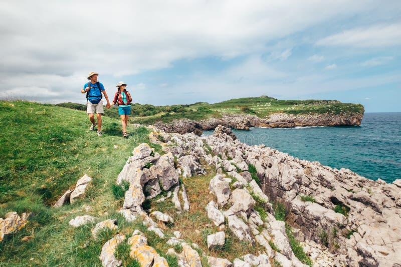 夫妇背包徒步旅行者旅客在海洋岩石海岸走 免版税库存照片