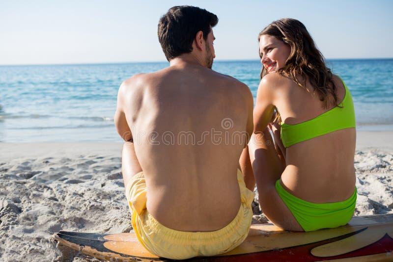夫妇背面图坐冲浪板在海滩 免版税库存照片