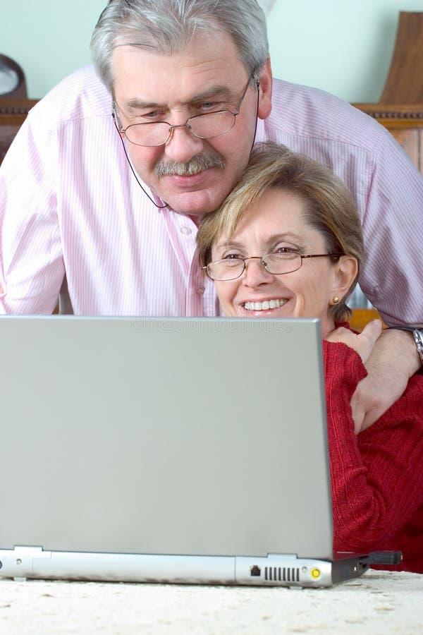 夫妇膝上型计算机成熟使用 库存照片
