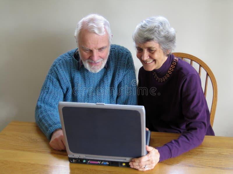 夫妇膝上型计算机查找前辈 免版税库存图片