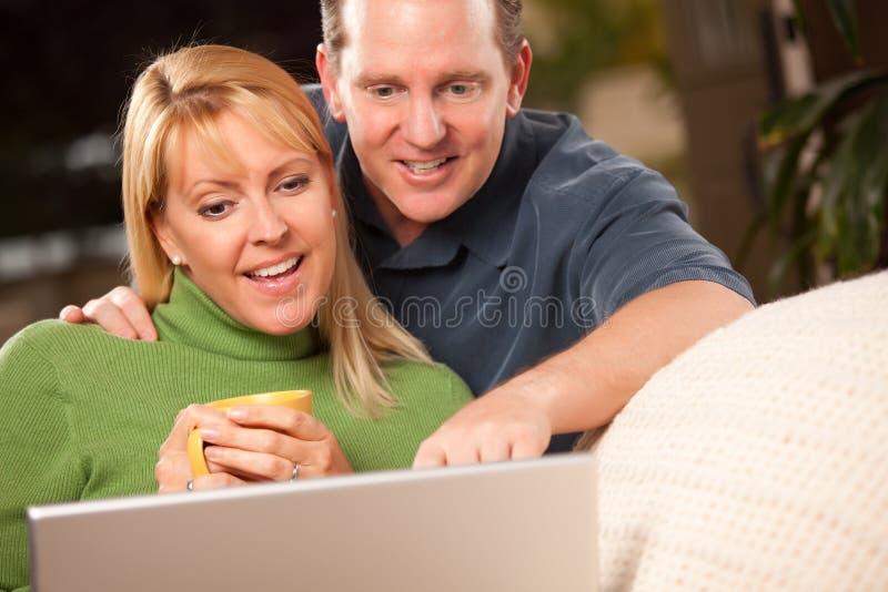 夫妇英俊的膝上型计算机使用 免版税图库摄影