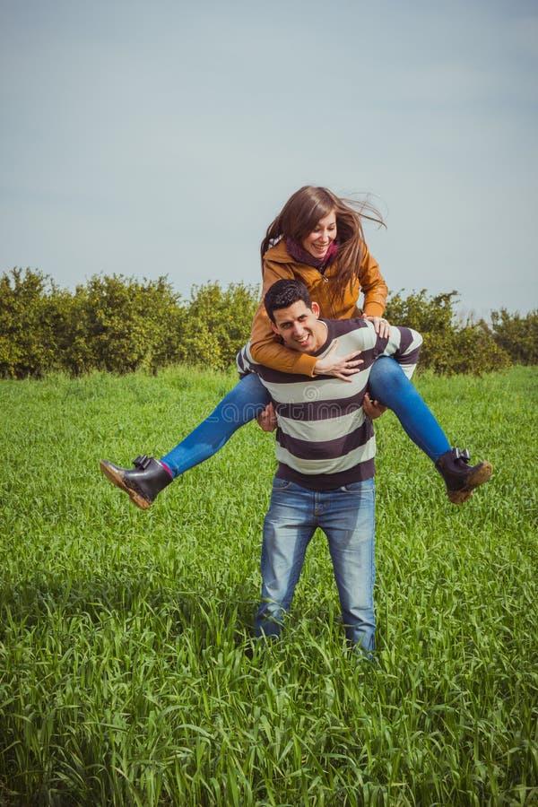 年轻夫妇获得乐趣一起在绿色领域 妇女ridin 免版税库存照片