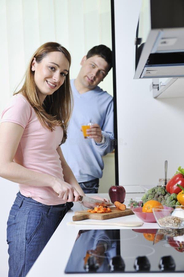 夫妇获得乐趣准备健康食物在厨房 免版税库存照片