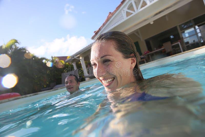 夫妇获得乐趣在游泳池 免版税库存照片