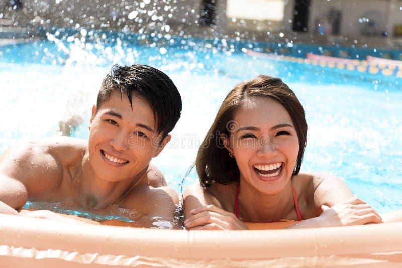 年轻夫妇获得乐趣在游泳池 图库摄影