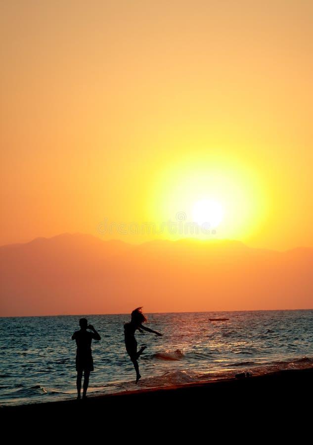夫妇获得在海滩的乐趣在日落 免版税库存照片