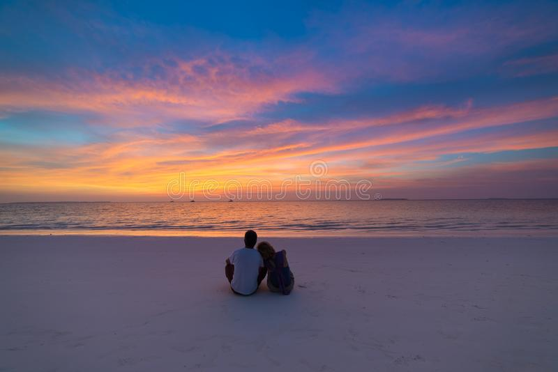 夫妇观看的日落天空坐沙滩浪漫天空在日落,背面图,金黄cloudscape,真人拥抱 库存照片