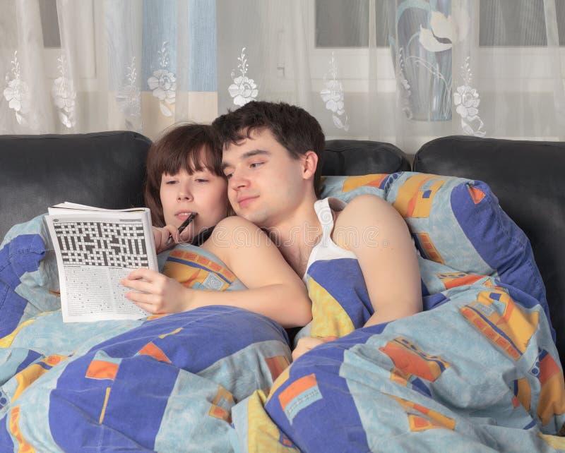 夫妇解决年轻人的纵横填字游戏 免版税图库摄影