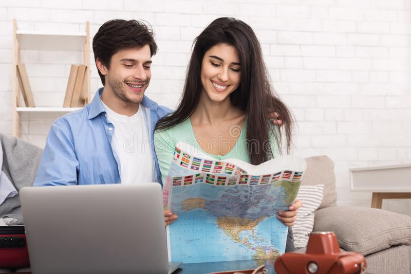 夫妇计划的假期,搜寻在地图的最佳的路线 免版税图库摄影