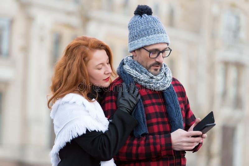 夫妇读在智能手机的消息 妇女拥抱有多孔的人 帽子和玻璃的人接受了SMS 库存照片