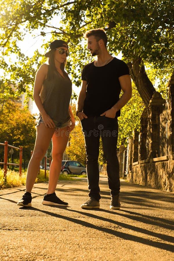 年轻夫妇谈话在日落在一个城市环境里 图库摄影