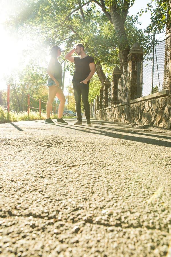 年轻夫妇谈话在日落在一个城市环境里 免版税库存照片