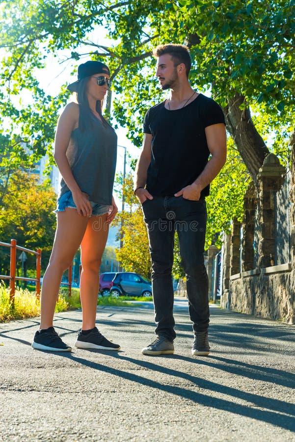 年轻夫妇谈话在日落在一个城市环境里 免版税库存图片