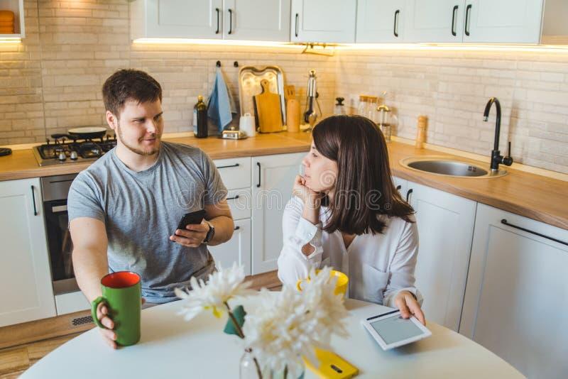 夫妇谈话在早晨饮用的茶的厨房 库存照片