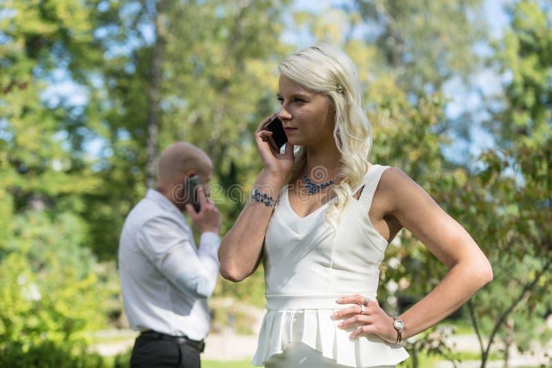 夫妇谈话在流动或巧妙的电话 男人和妇女与电话讲话 青年人为电话使用手机在公园 库存照片