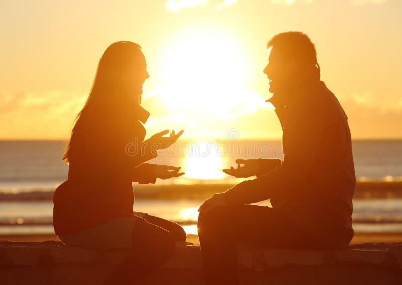 夫妇谈话在海滩的日落 库存照片