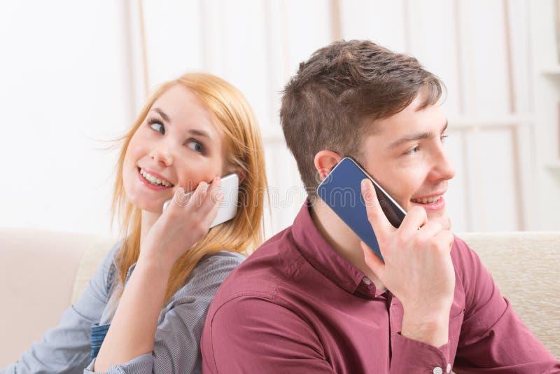 夫妇谈话在他们的智能手机 免版税库存图片