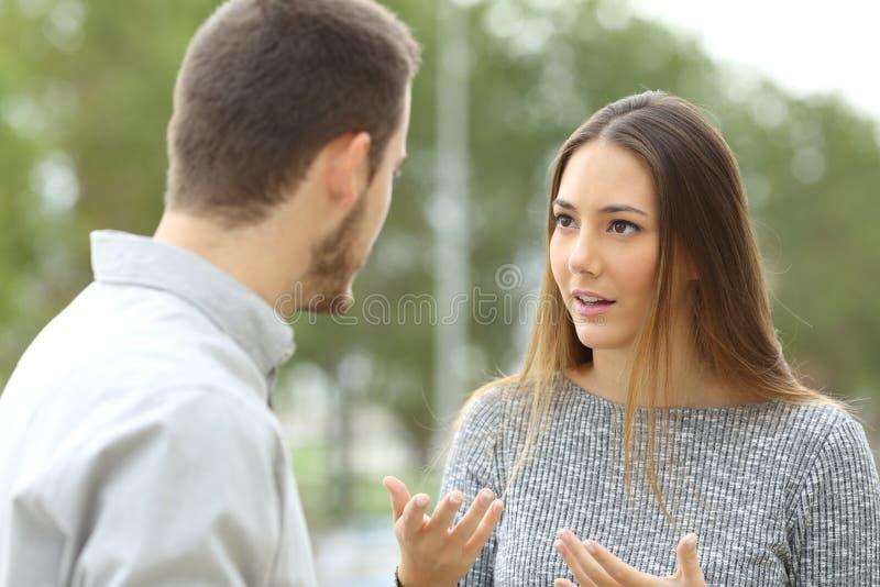 夫妇谈话户外在公园 免版税图库摄影