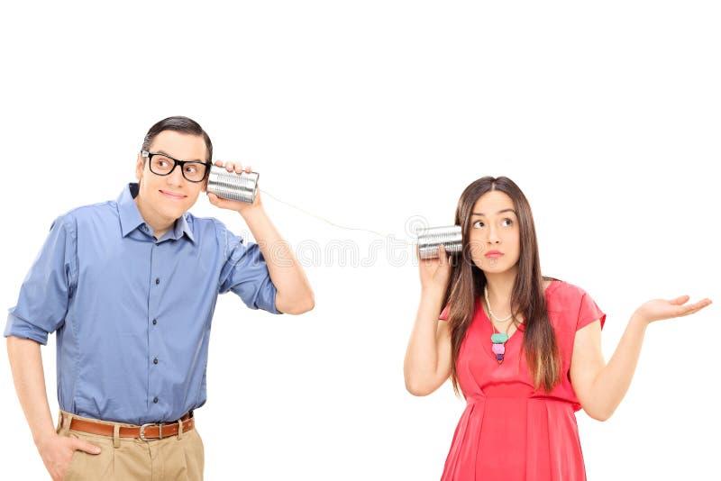 年轻夫妇谈话通过锡罐打电话 库存照片
