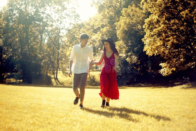 夫妇跑在森林里的,领域 一个长的红色礼服和帽子的,时髦地加工好的人女孩 r ?? 免版税库存照片