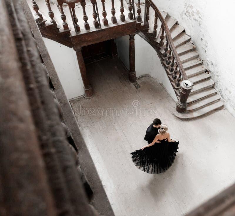 年轻夫妇跳舞的画象在黑衣服和礼服的 婚姻 库存照片