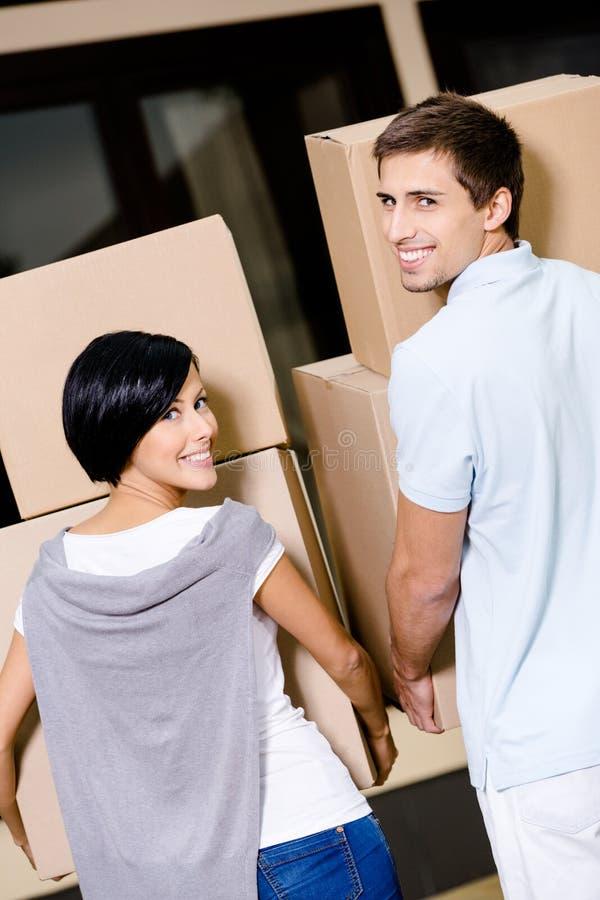 夫妇运载的纸板箱回到视图  库存图片