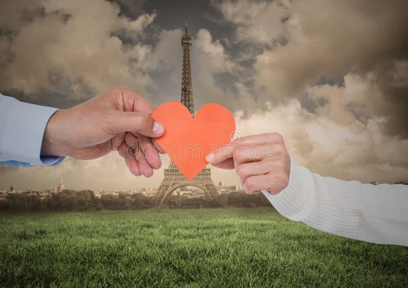 夫妇递拿着心脏反对数位引起的埃佛尔铁塔在距离 库存图片