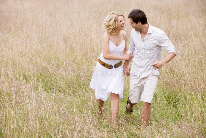 夫妇递暂挂户外微笑的走 免版税图库摄影