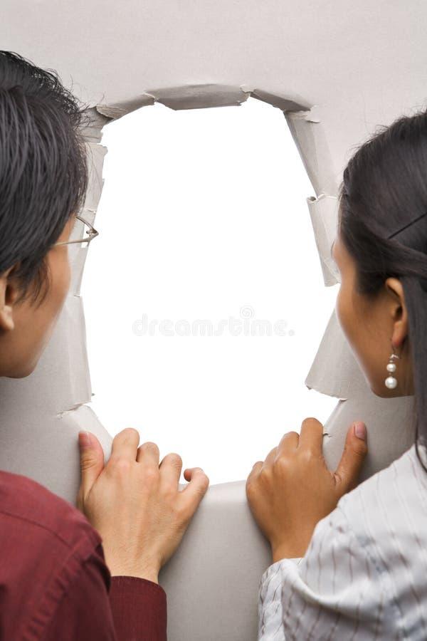 夫妇钻孔偷看墙壁 库存图片