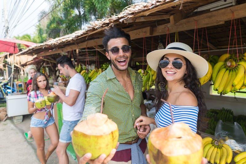 夫妇饮料椰子亚洲人果子买新鲜食品、年轻人和妇女游人异乎寻常的假期的街市 免版税图库摄影