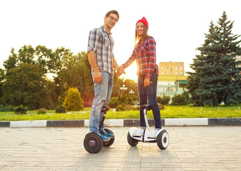年轻夫妇骑马hoverboard -电子滑行车,个人EC 免版税库存图片