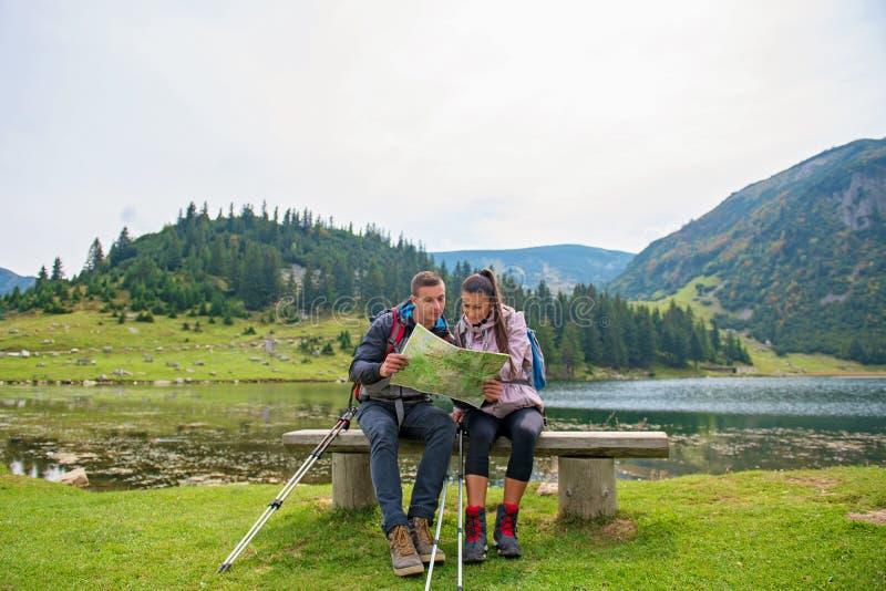 夫妇高涨 年轻加上看在湖旁边的背包地图 免版税库存照片