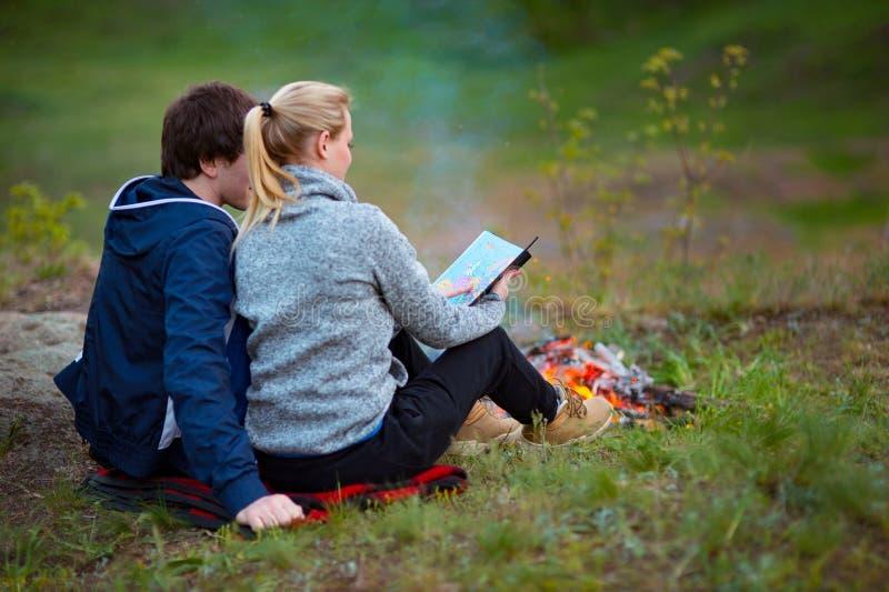 夫妇高涨 年轻夫妇坐在火附近拥抱和审查地图的草 旅行,假期,假日和 免版税库存图片