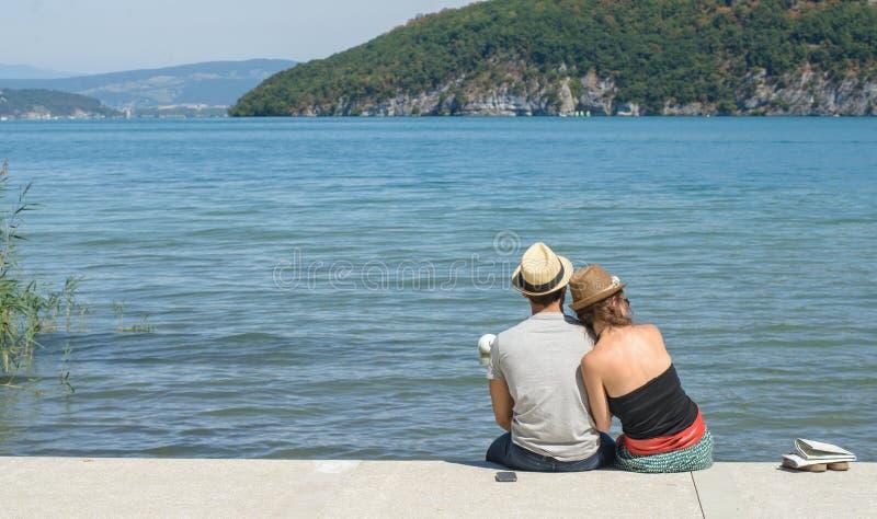夫妇,后面看法,坐在水附近 库存照片