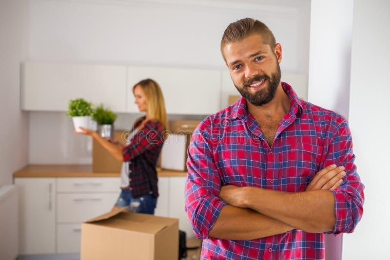 年轻夫妇移动向他们新的公寓 可爱的男孩a 免版税库存图片
