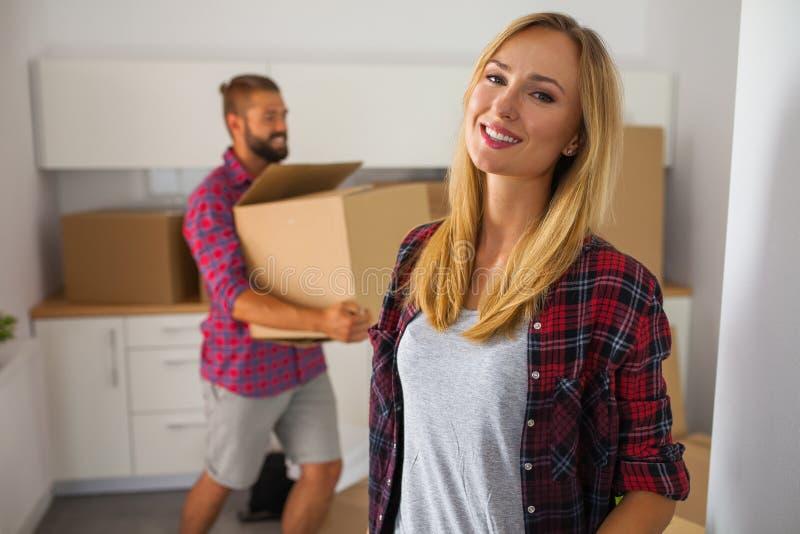 年轻夫妇移动向他们新的公寓 美丽的女孩 图库摄影