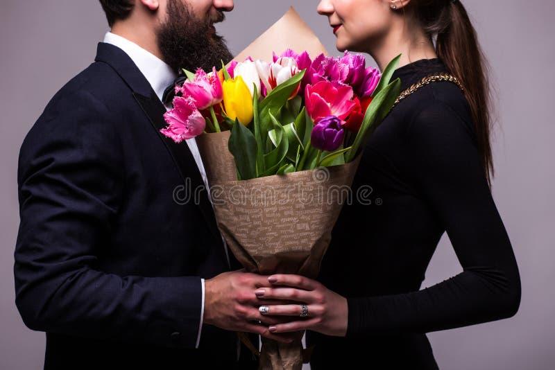 年轻夫妇画象爱上摆在演播室的花郁金香的在灰色backround的经典衣裳穿戴了 库存图片
