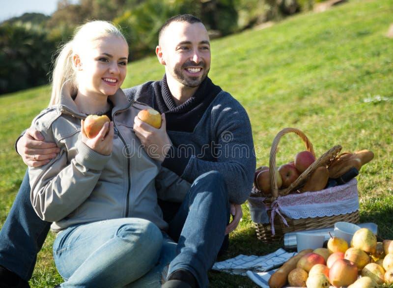 夫妇lounging在户外野餐 免版税库存图片