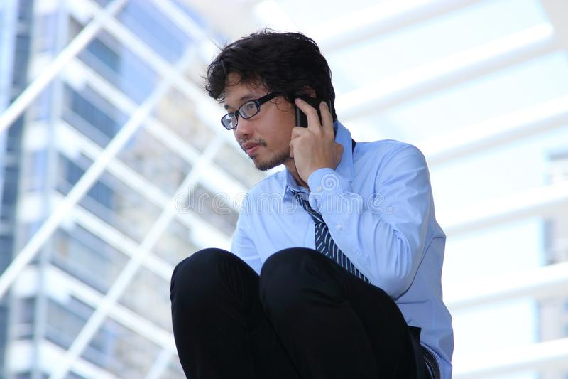 失业的年轻亚洲商人谈流动巧妙的电话在都市大厦背景 沮丧的失业企业concep 免版税库存照片
