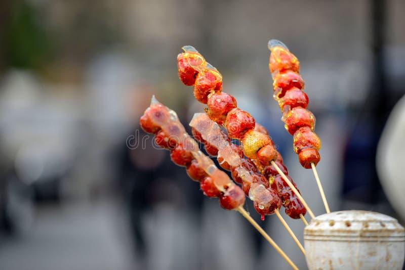 失去作用用在棍子的焦糖的果子在街道前门上在贝吉 免版税库存图片