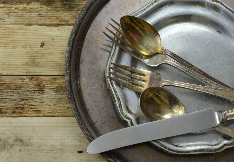 失去光泽的银顶上的透视镀了平的商品和盛肉盘与在土气木桌背景的破旧的奖杯盘 警察 免版税图库摄影
