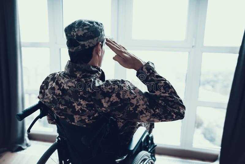 失去能力在轮椅的军服致敬 免版税图库摄影