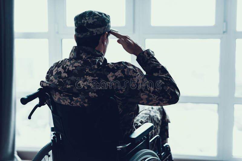 失去能力在轮椅的军服致敬 免版税库存图片