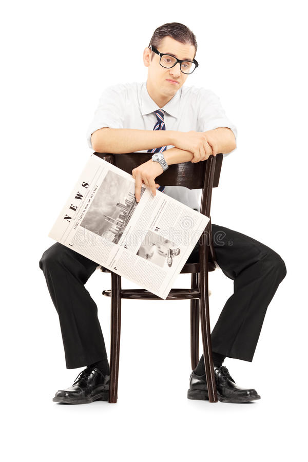 失望的买卖人坐与报纸的一把椅子 库存照片