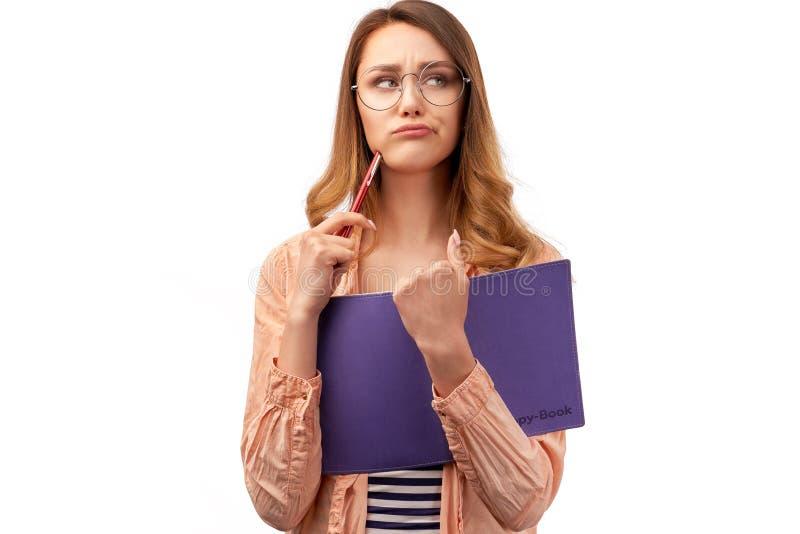 失望的女生皱眉面孔,感觉疲乏乏味填入的材料,举行打开了书,愤怒看在旁边 库存图片
