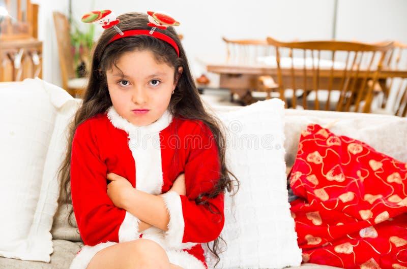 失望的小女孩佩带的圣诞节礼服 免版税图库摄影