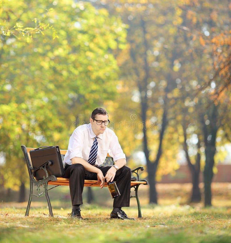失望的年轻商人坐与瓶的一条长凳 库存照片