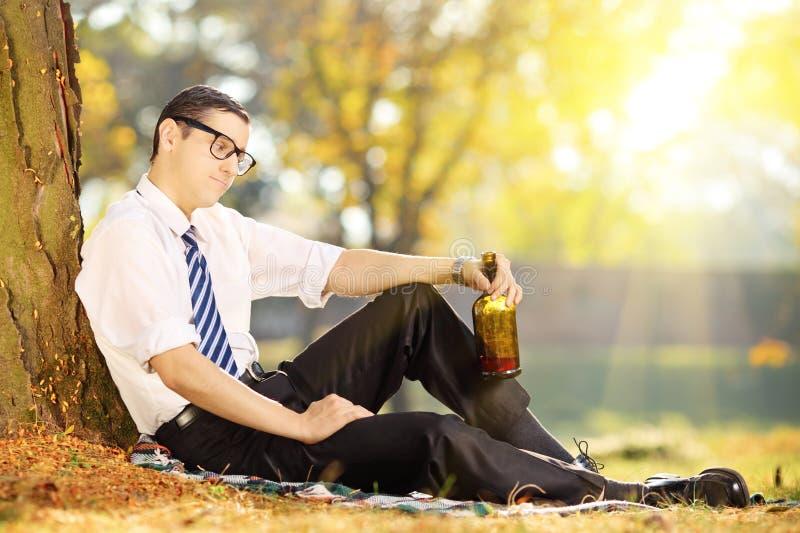失望的年轻商人坐与瓶的一棵草 图库摄影